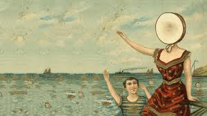 Image of a lady with a drum over her head by the sea.