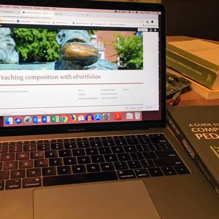 Photograph of a laptop open to a Wordpress page. Several books on composition sit next to it.