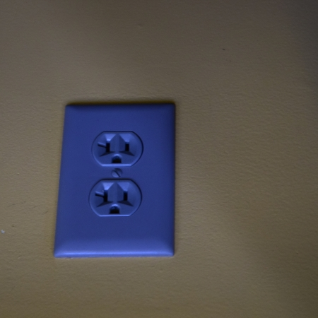 A blue electrical outlet on a wall.